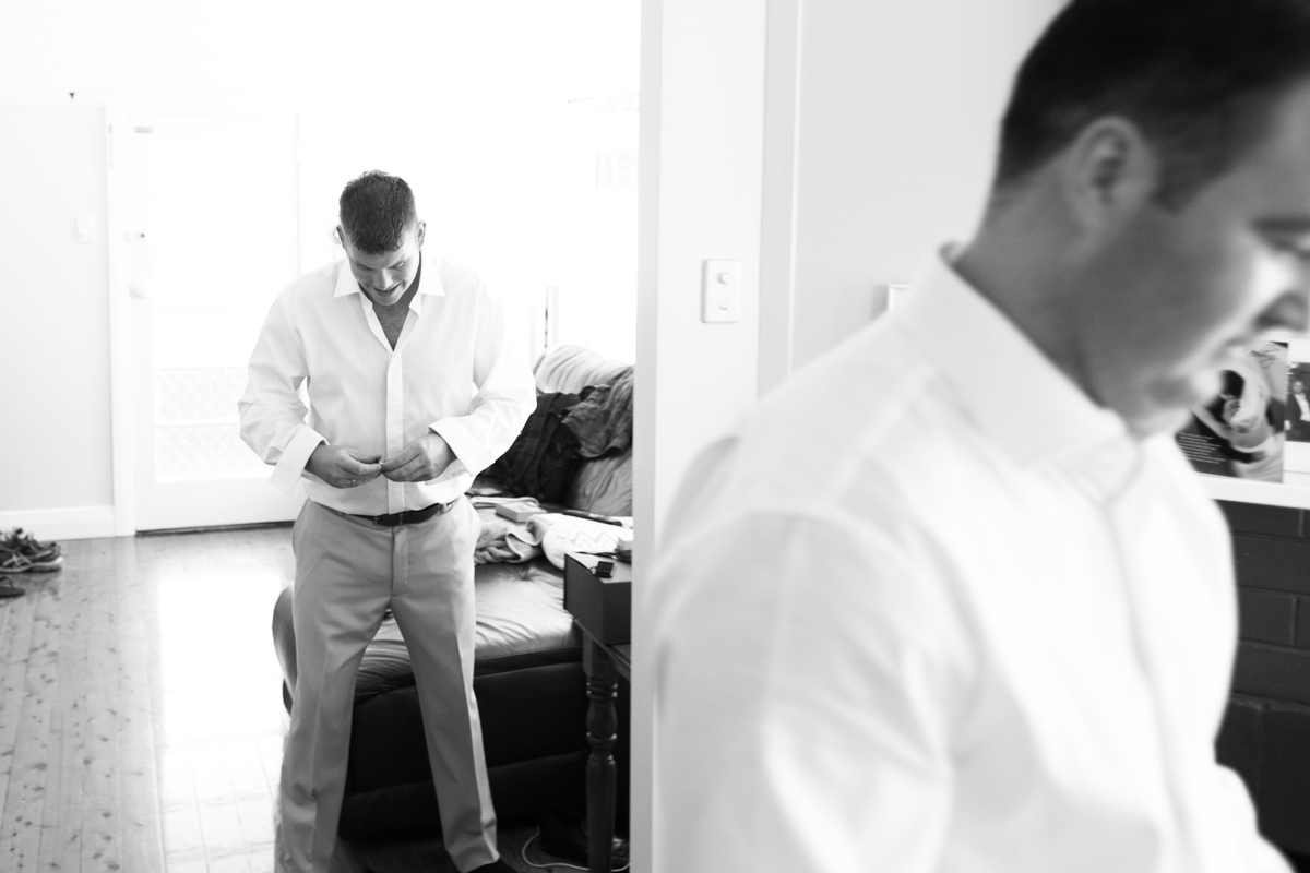 Black and white shot of the groom buttoning up his white shirt while his groomsman walks past in the foreground Caves Beach wedding photography