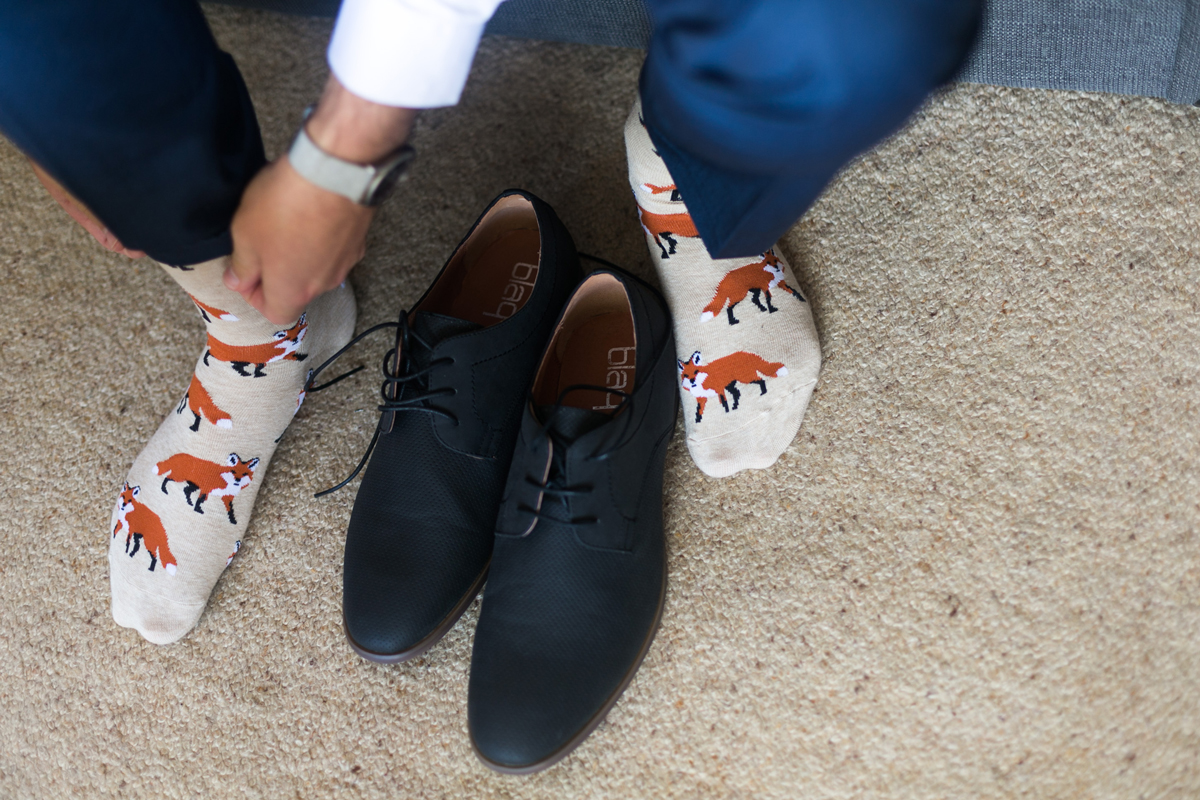 Close up of the groom's navy lace-up shoes and fox print socks as he gets ready for his Tocal Homestead wedding photographer