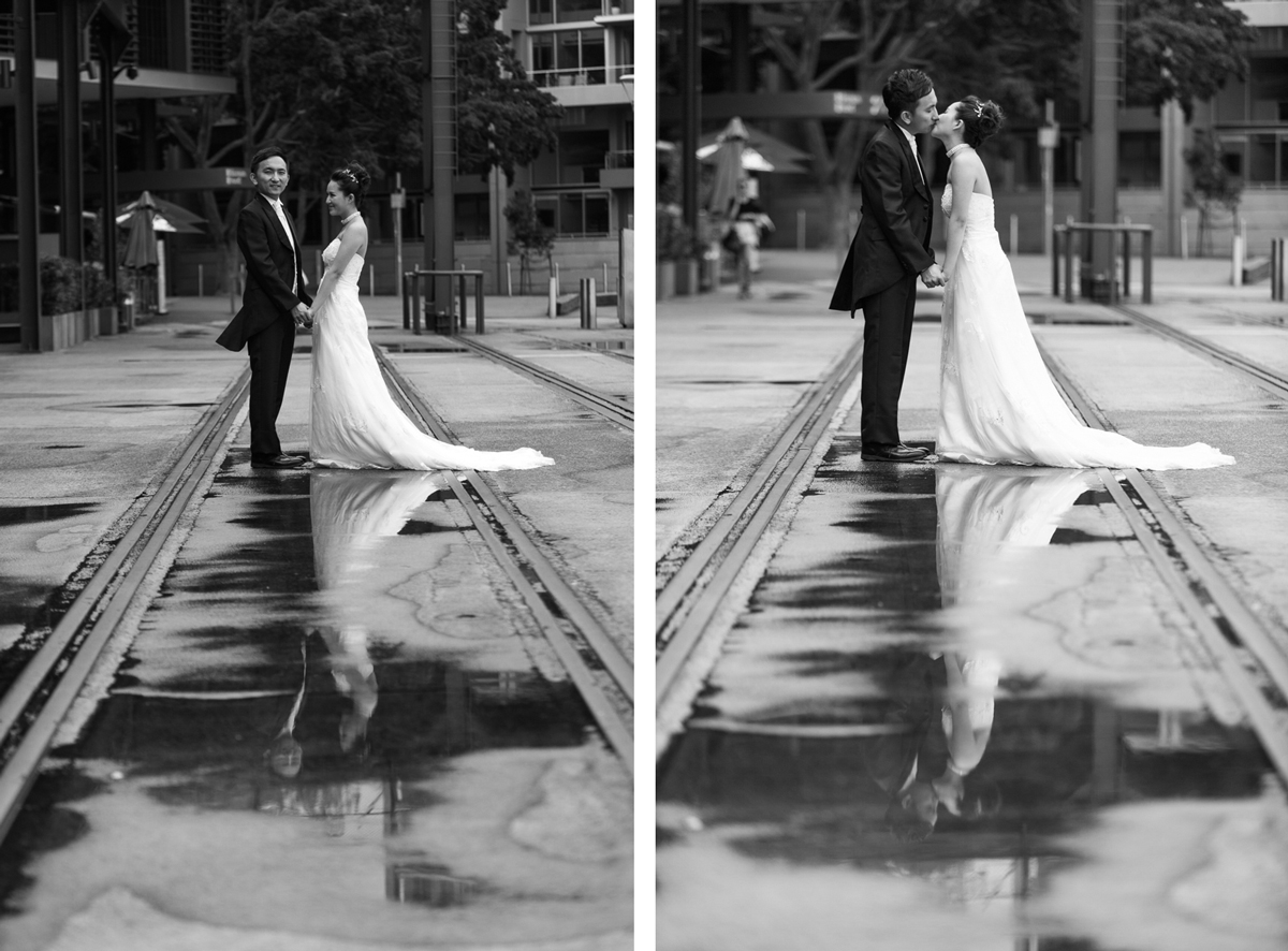 Black and white dual shot of the bride and groom standing on the old train tracks at the Rocks in Sydney holding hands and kissing while they are reflected in puddles on the ground Sydney wedding photographer