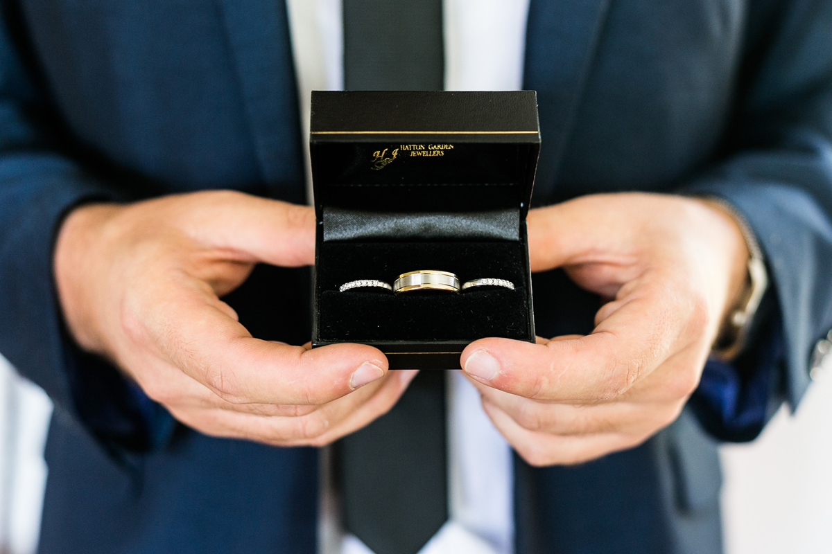 Close up of the wedding bands in their box held by the groom wearing a navy blue suit Tocal Homestead wedding photographer