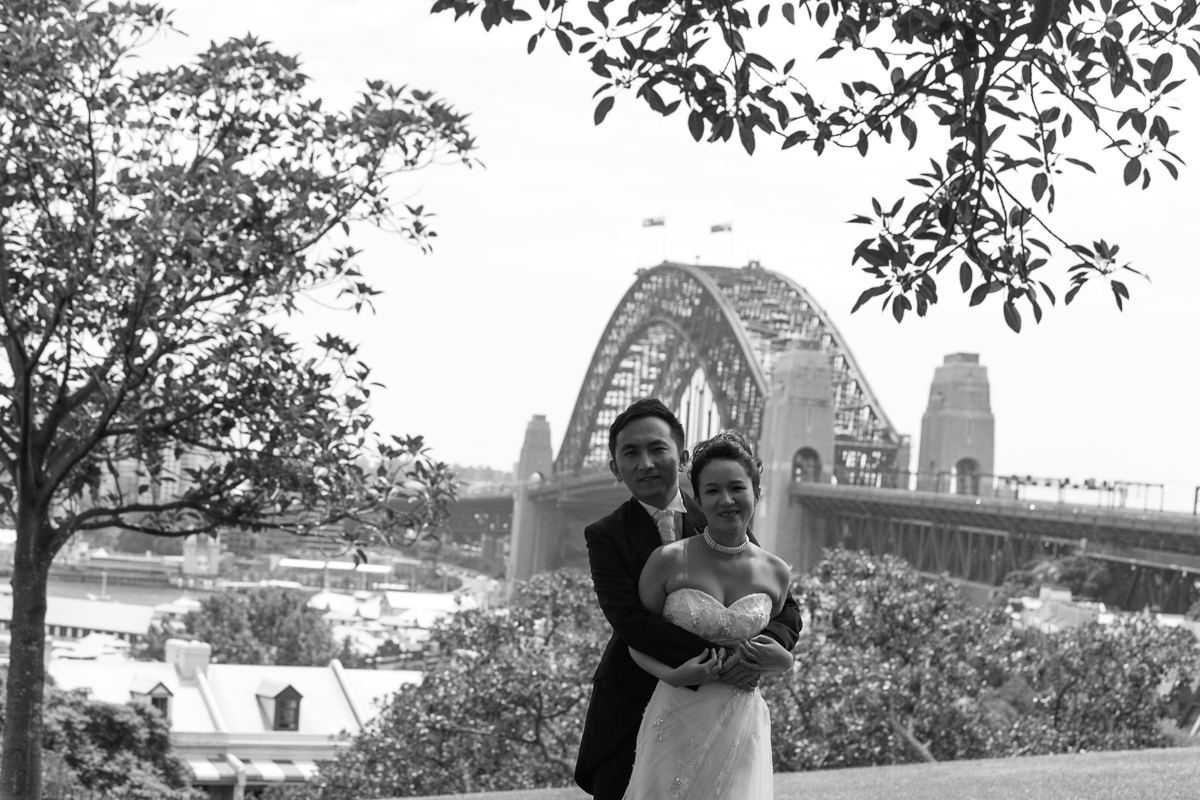 Black and white shot of the bride and groom embracing facing the camera with the Sydney Harbour Bridge in the background Sydney wedding photographer