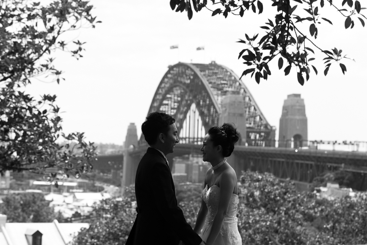 Black and white landscape shot of the bride and groom holding hands with the Sydney Harbour Bridge in the background Sydney wedding photographer