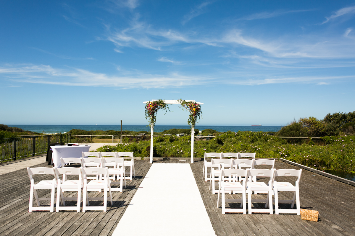 Landscape shot of the wedding ceremony location on a rustic deck overlooking the beach with a white archway decorated with multicoloured flowers and greenery with white deck chairs and a white aisle runner Caves Beach wedding photography