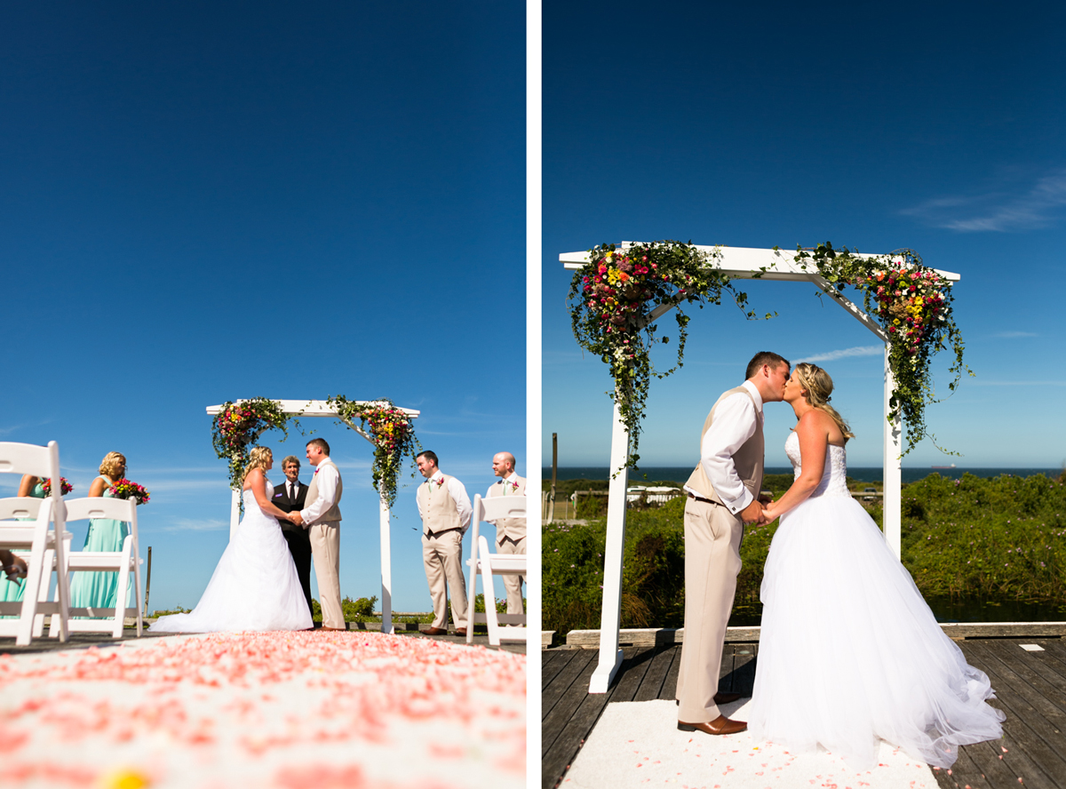 Dual shot of the bride and groom at the altar holding hands, and kissing under the white wooden arch with an expanse of blue background behind them and pink rose petals on the white aisle runner Caves Beach wedding photography