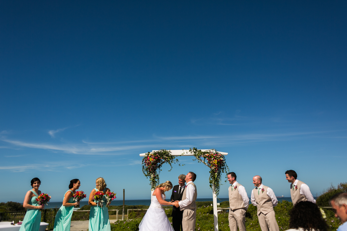 Landscape shot of the bride and groom holding hands and laughing during their wedding ceremony flanked by their bridesmaids and groomsmen with an expanse of blue sky in the background Caves Beach wedding photography