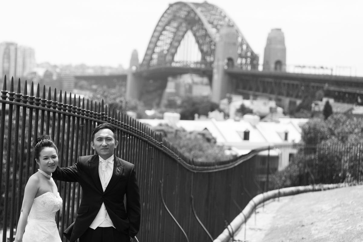 Black and white shot of the bride and groom leaning against a wrought iron fence with the Sydney Harbour Bridge in the background Sydney wedding photographer