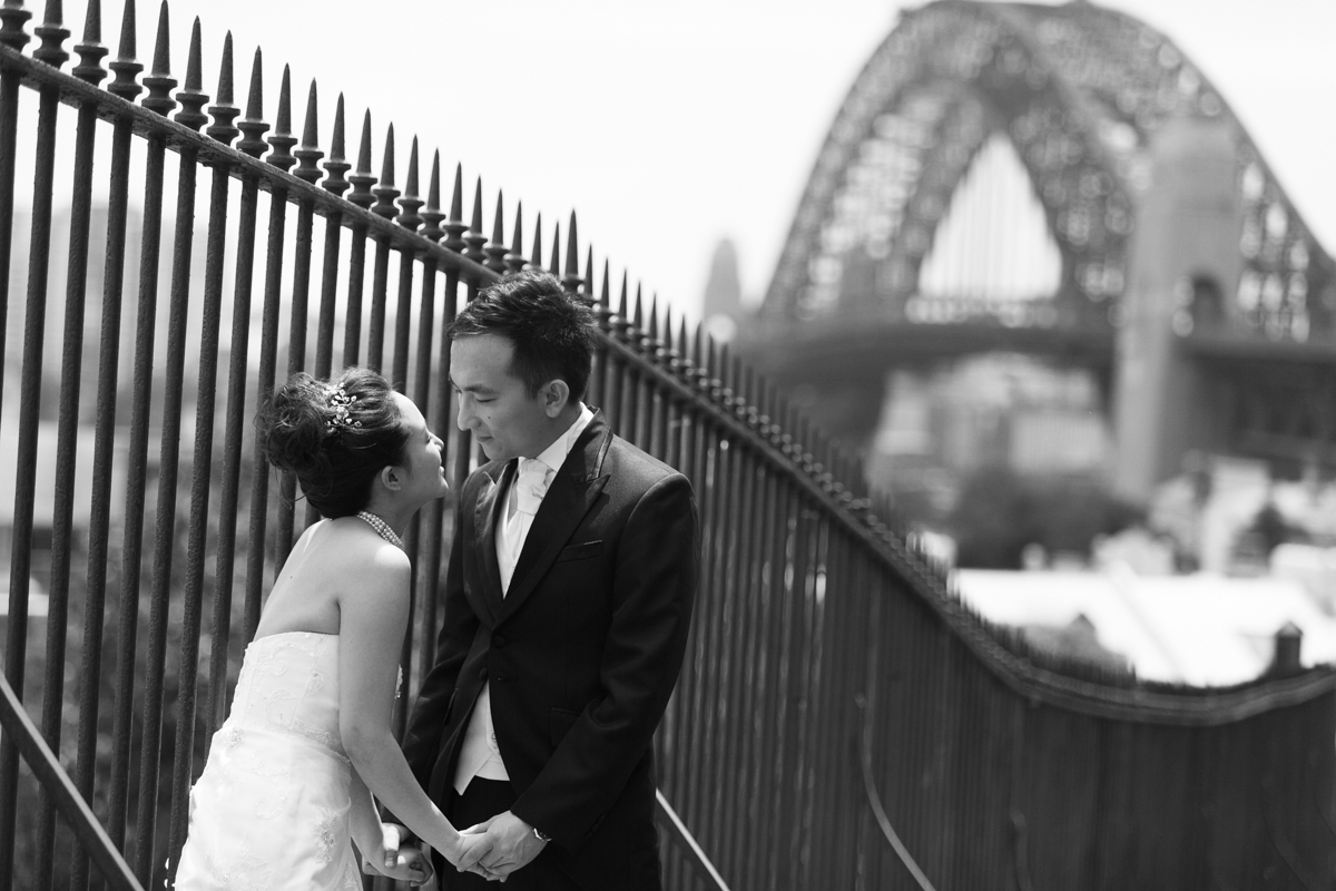 Candid shot of the bride and groom looking into each others eyes standing next to a black iron fence with the Sydney Harbour Bridge in the background Sydney wedding photographer