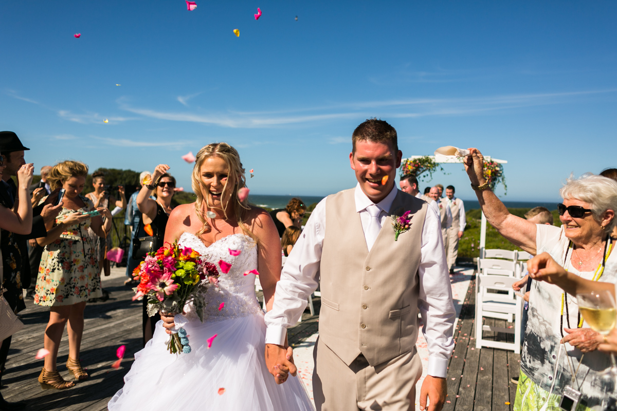Candid shot of the bride and groom walking back down the aisle while their wedding guests throw rose petals over them Caves Beach wedding photography