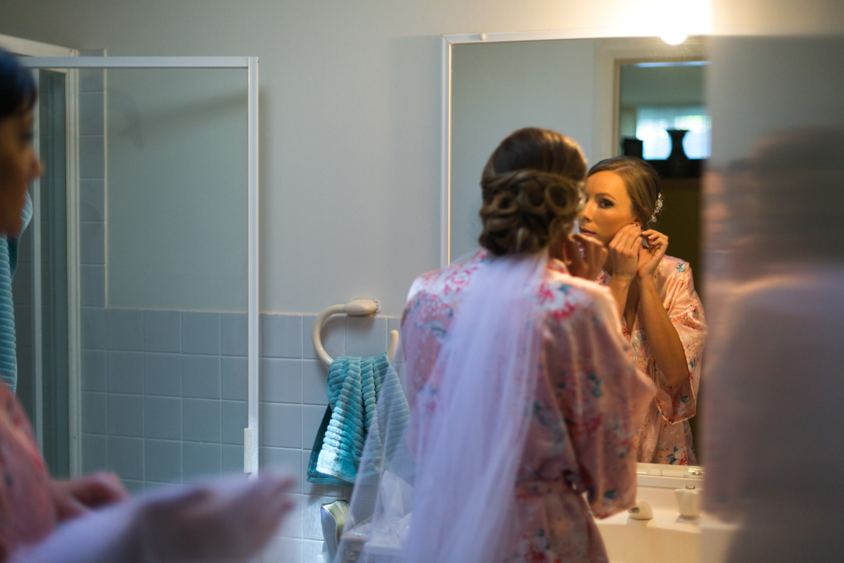 Candid shot of the bride putting her earrings in wearing a pink kimono and her veil Tocal Homestead wedding photographer