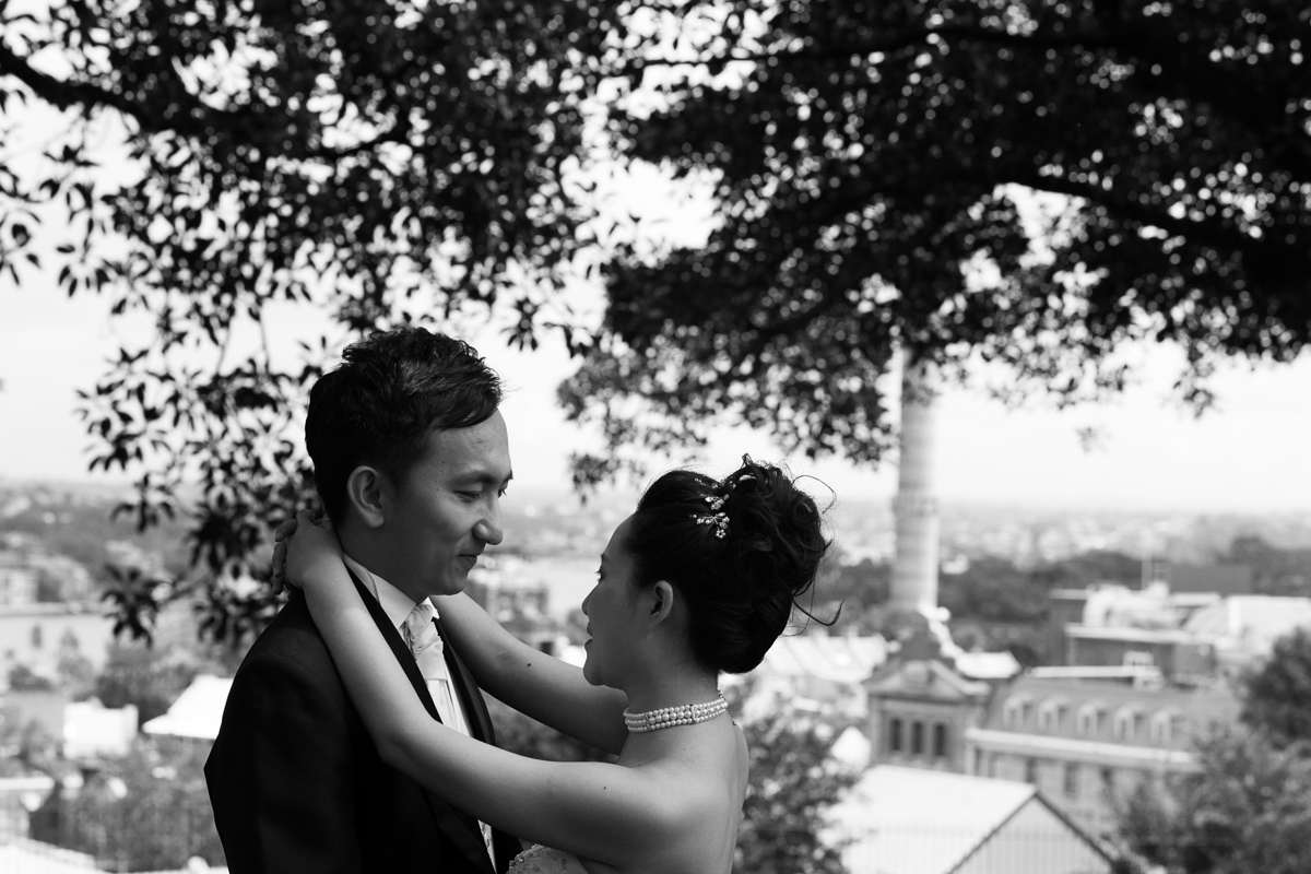Black and white shot of the bride and groom gazing into each others eyes with the cityscape of Sydney in the background Sydney wedding photographer