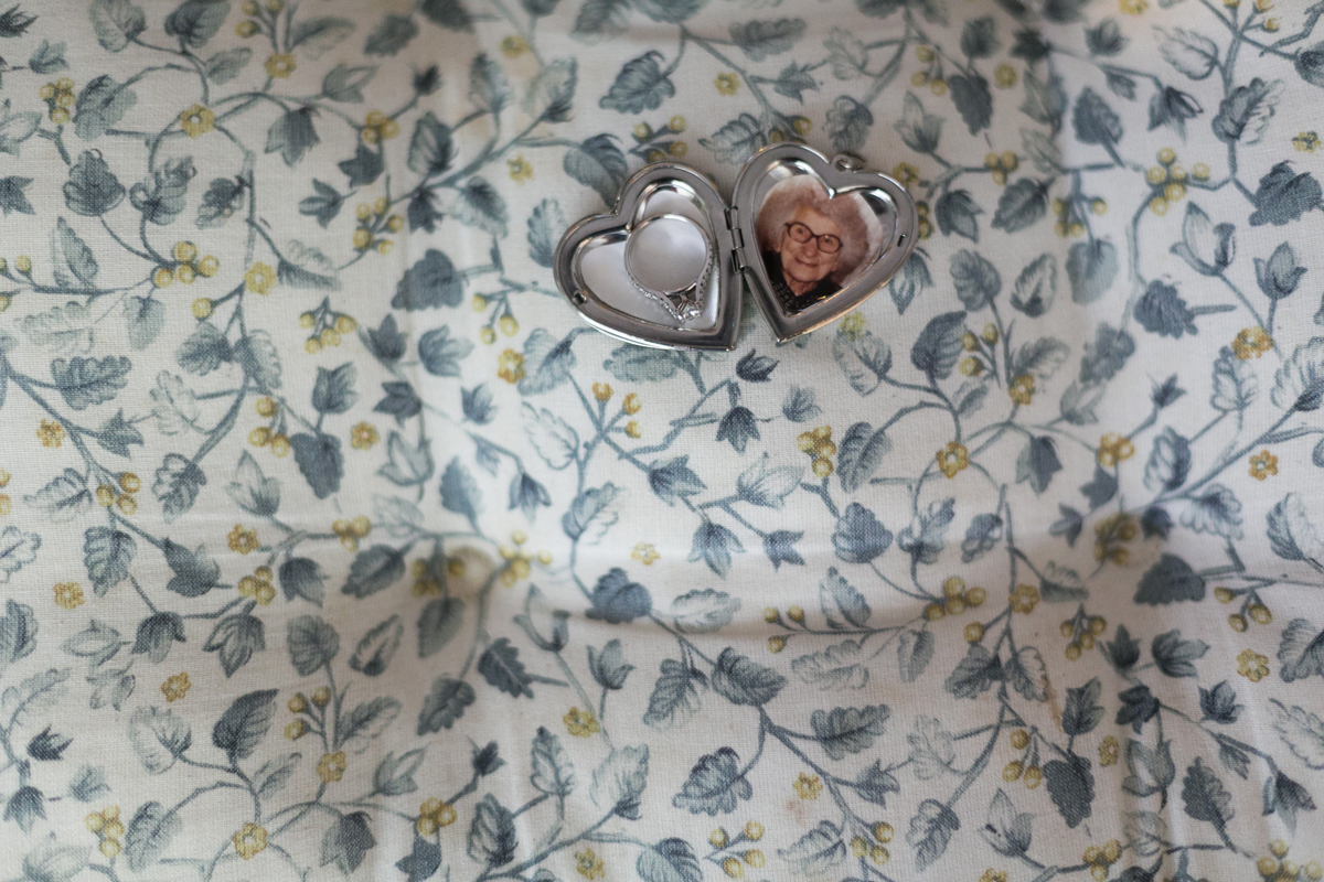 Close up of a silver heart locket open showing a photo of grandmother and the bride's engagement ring on a blue floral tablecloth Tocal Homestead wedding photographer