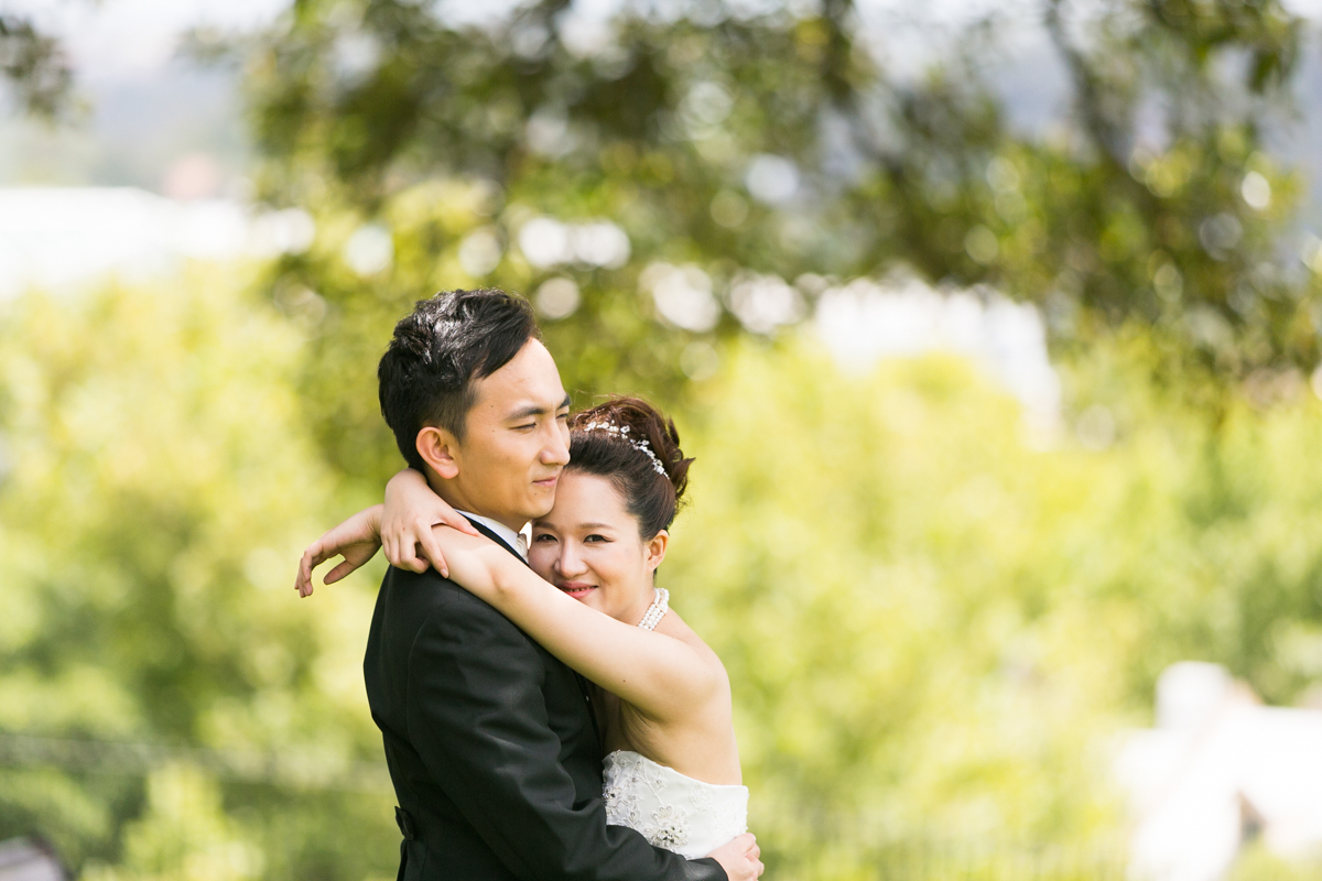 The bride and groom standing with their arms around each other with unfocused greenery in the background Sydney wedding photographer