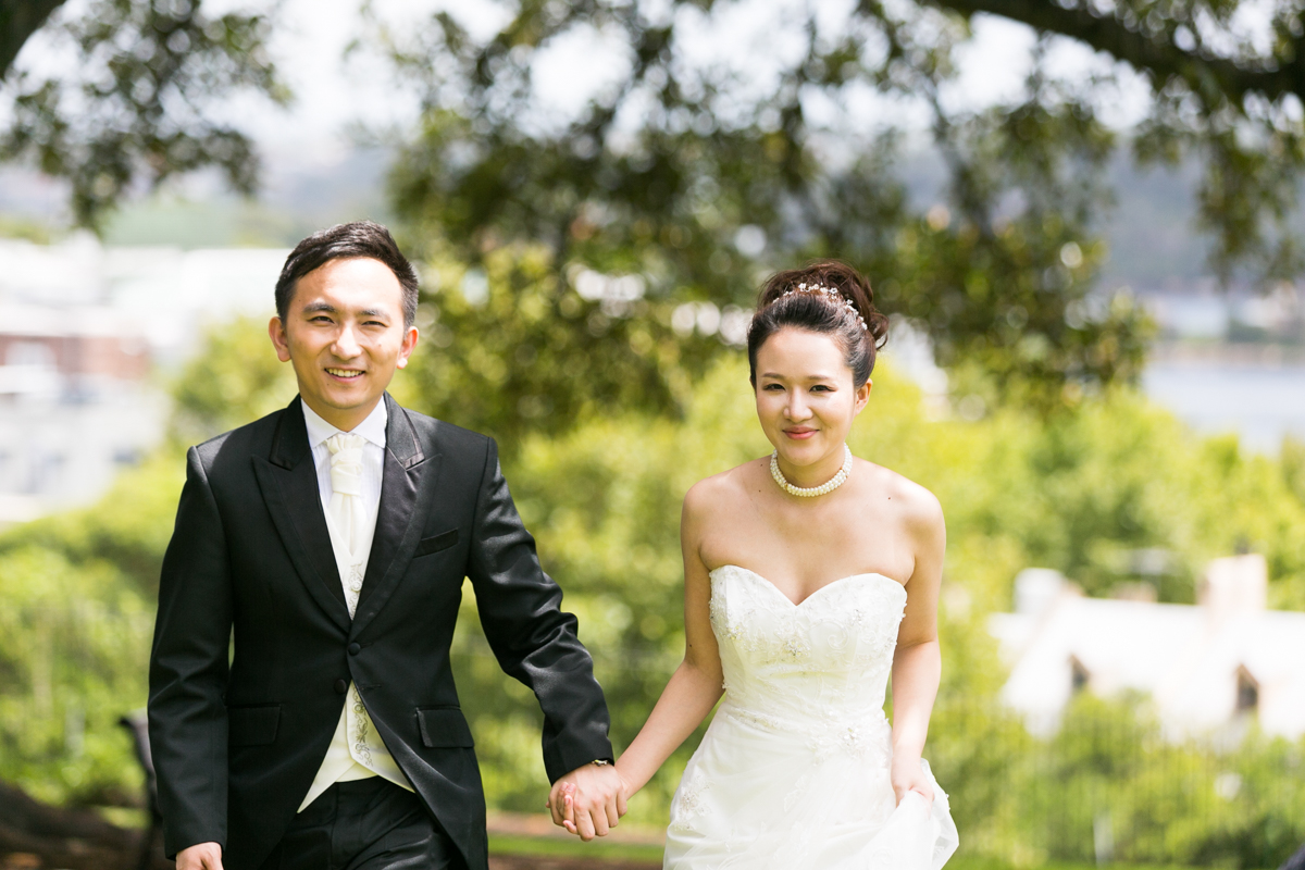 The bride and groom walk toward the camera holding hands with unfocussed greenery in the background Sydney wedding photographer