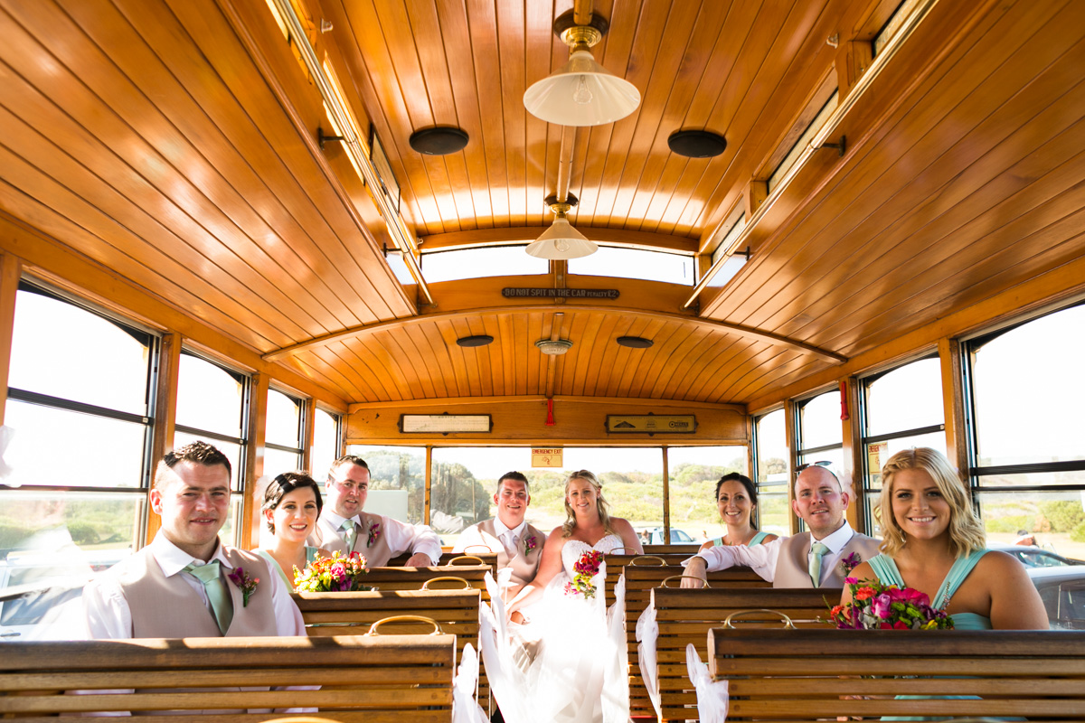 The bride and groom sit on Newcastle's Famous Tram with their bridal party Caves Beach wedding photography