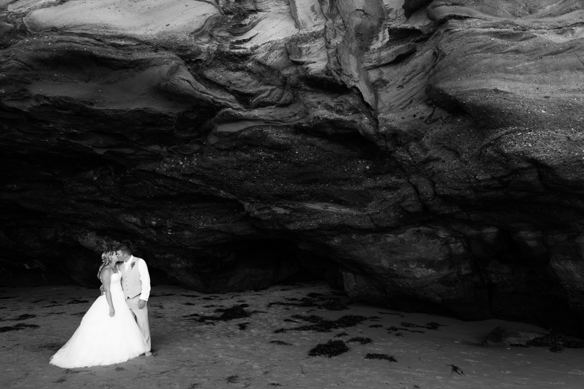 Black and white shot of the bride and groom kissing standing in a natural beach cave Caves Beach wedding photography