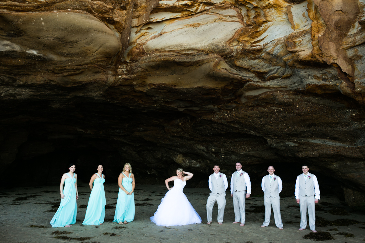 Candid shot of the bride striking a pose flanked by her groom and bridal party standing in the mouth of a natural rock beach cave Caves Beach wedding photography