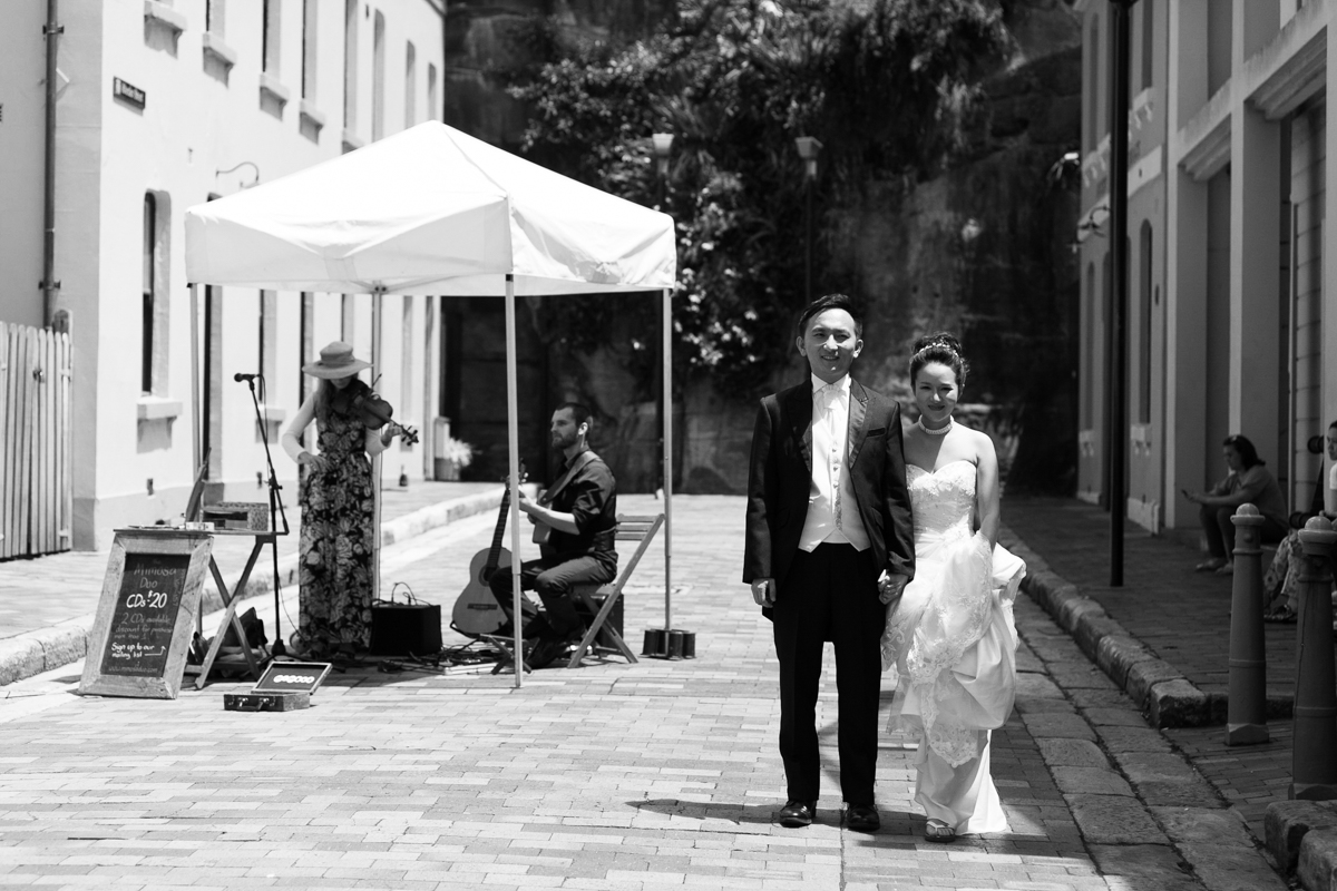 Black and white shot of the bride and groom stand holding hands in a cobblestoned alley while a busker plays guitar behind Sydney wedding photographer