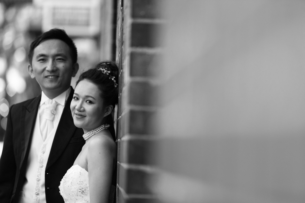 Black and white artistic shot looking down a brick wall toward the bride and groom who are leaning against the wall looking into the camera Sydney wedding photographer