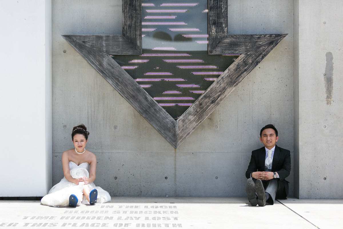 Artistic shot of the bride and groom seated in front of a cement wall under a lit up wooden arrow art installation at the Museum of Contemporary Art Sydney wedding photographer