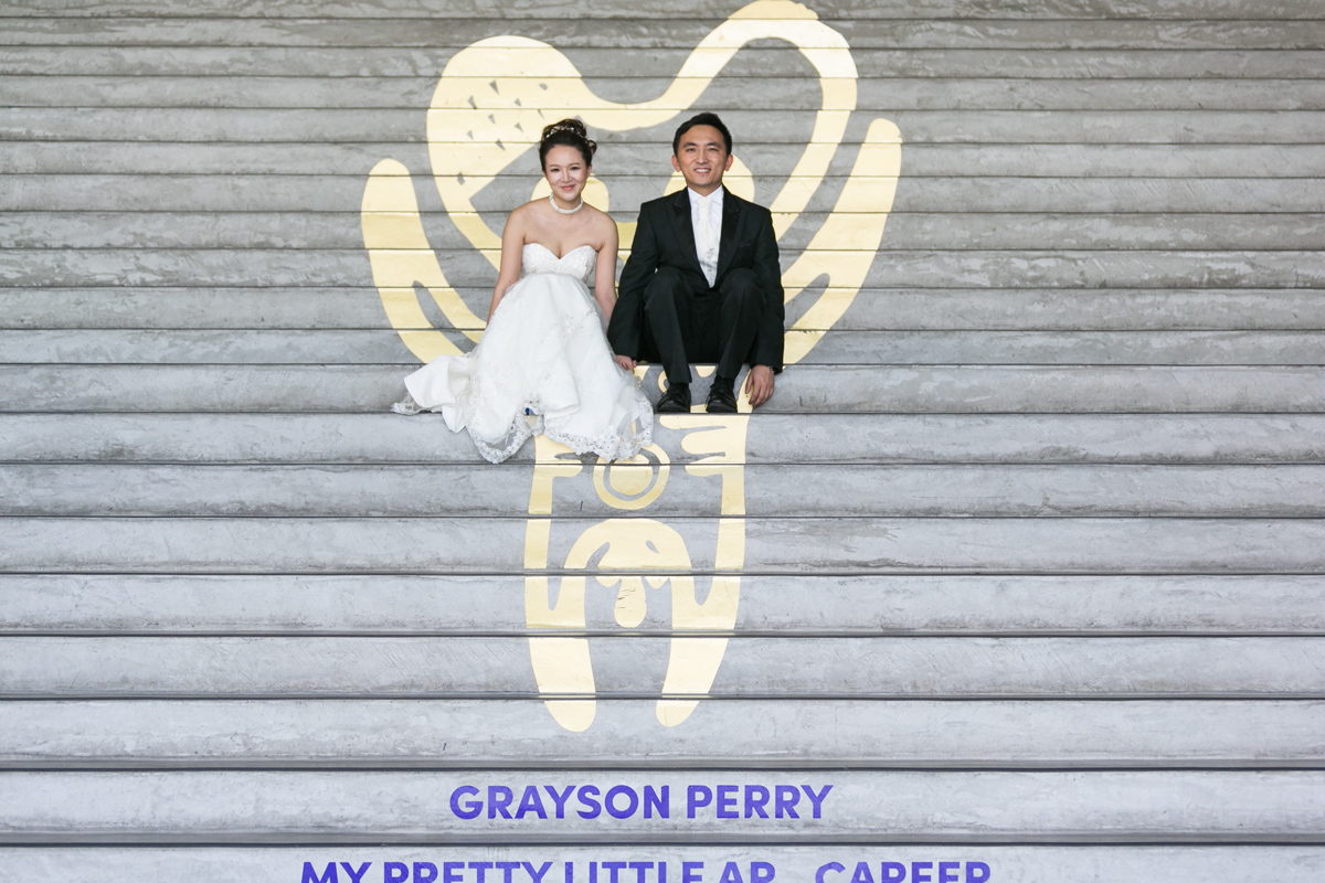 Artistic shot of the bride and groom sitting on cement steps decorated with a gold painted figure by Grayson Perry at the Museum of Contemporary Art Sydney wedding photographer