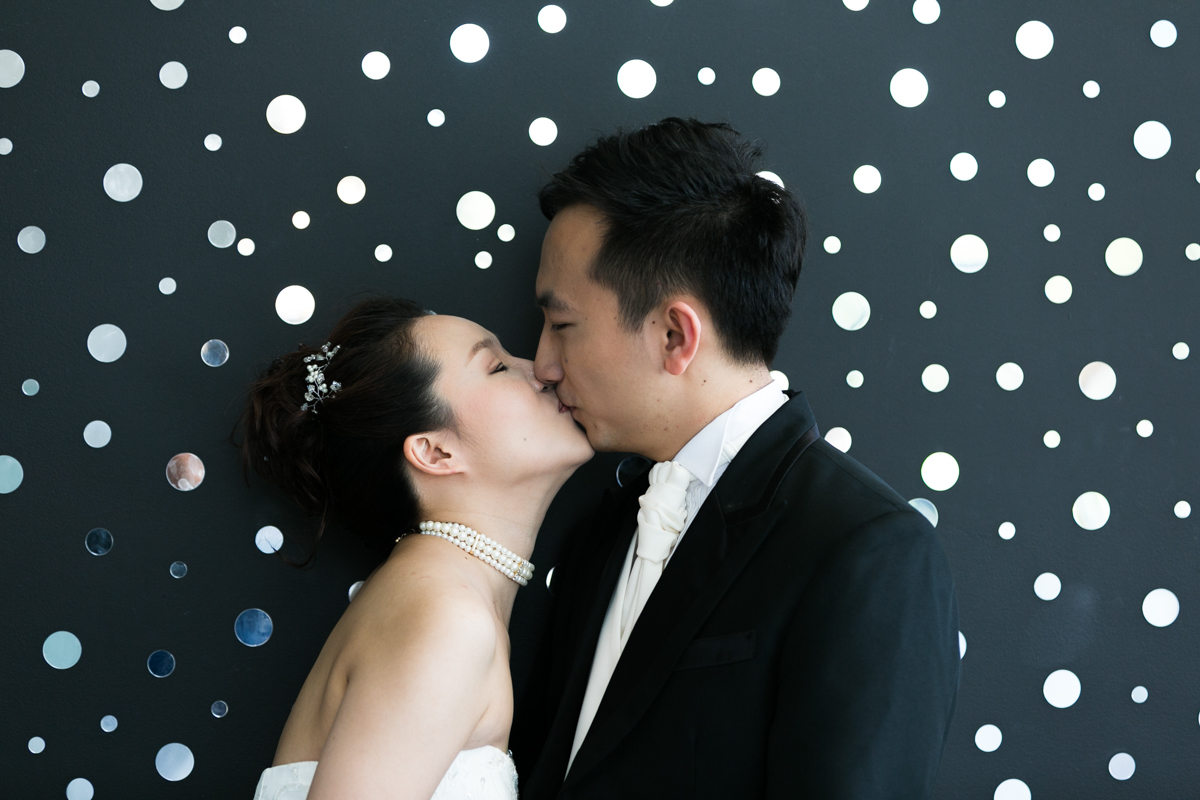 The bride and groom kiss in front of a black wall covered in small round mirrors at the Museum of Contemporary Art Sydney wedding photographer
