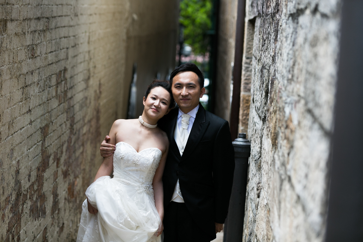 The bride and groom standing with their arms around each other in an old brick and sandstone alleyway in The Rocks Sydney wedding photographer