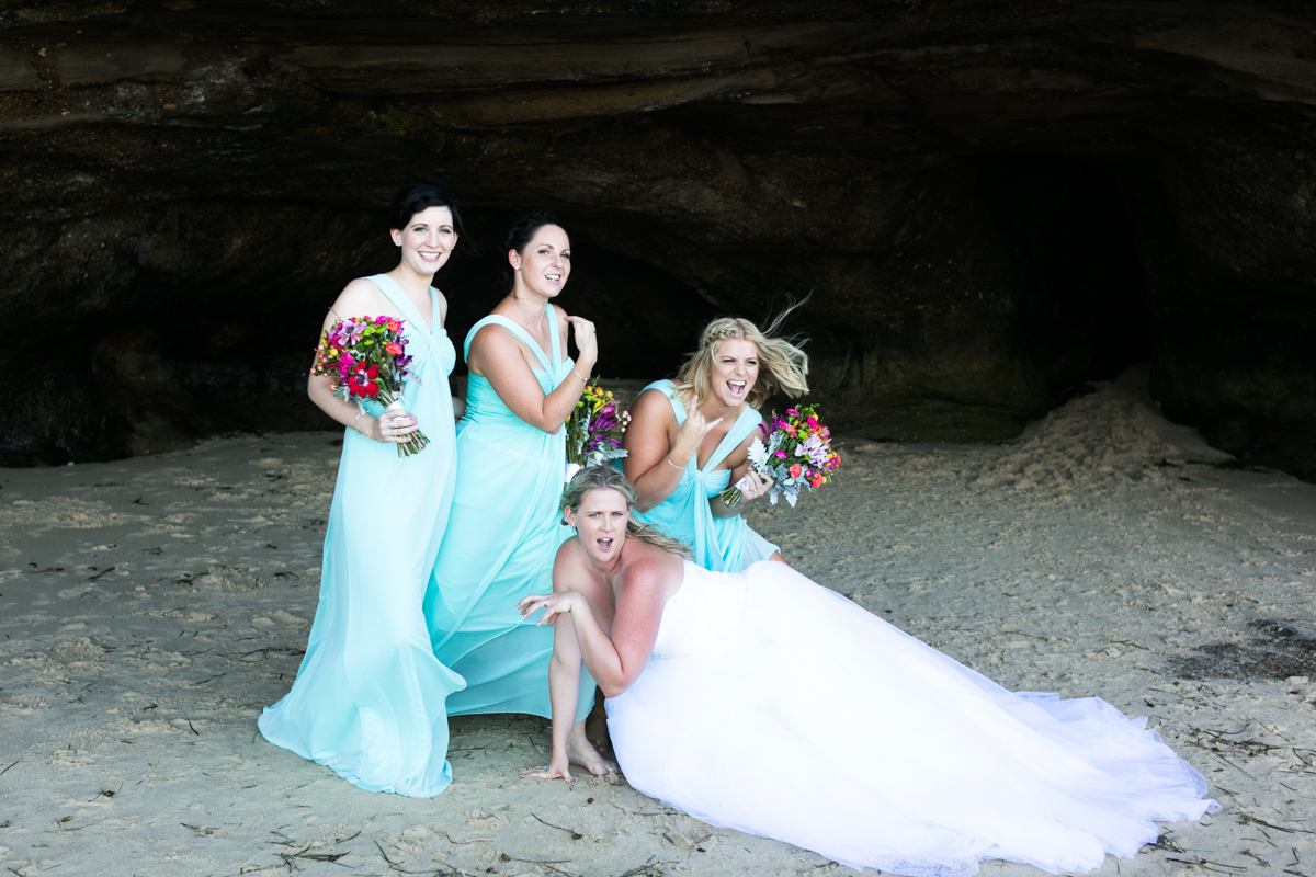 Candid shot of the bride and bridesmaids pulling silly faces and poses in the mouth of a natural beach cave Caves Beach wedding photography