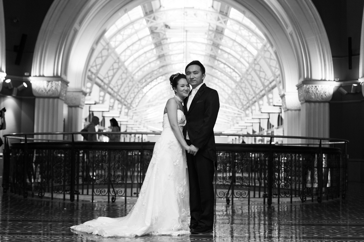 Black and white shot of the bride and groom standing together in the centre of the top floor of the Queen Victoria Building with the arched ceilings and the wrought iron railings behind Sydney wedding photographer