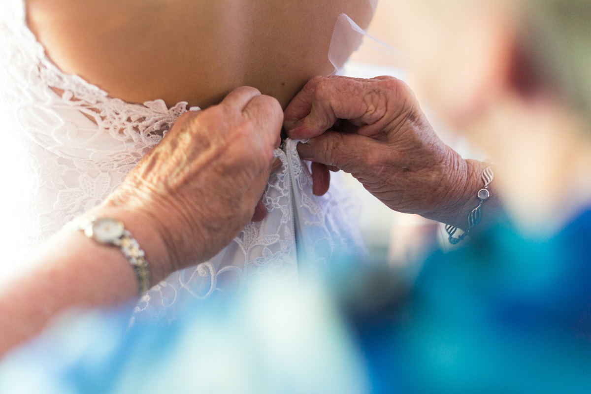 Close up of the bride's grandmother buttoning up the back of her white lace wedding dress Tocal Homestead wedding photographer