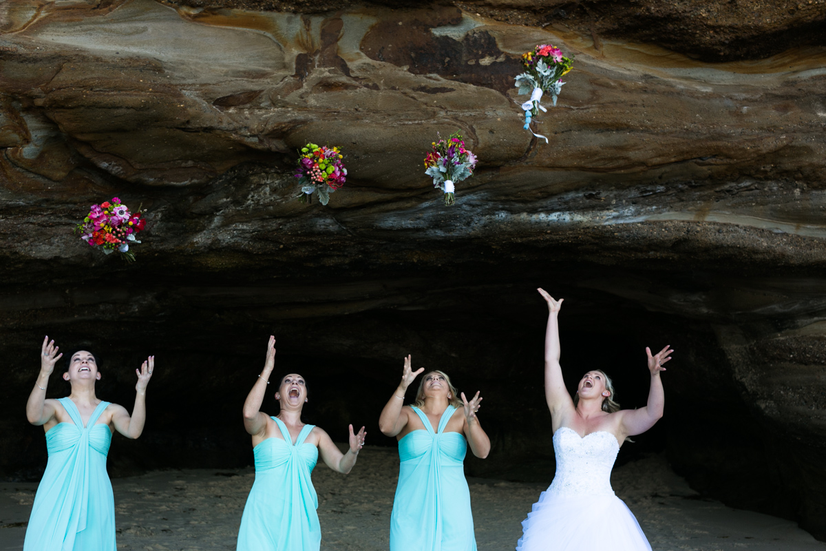 The bride and bridesmaids stand in a line in the mouth of a natural rock beach cave and throw their multicoloured flower bouquets in the air Caves Beach wedding photography