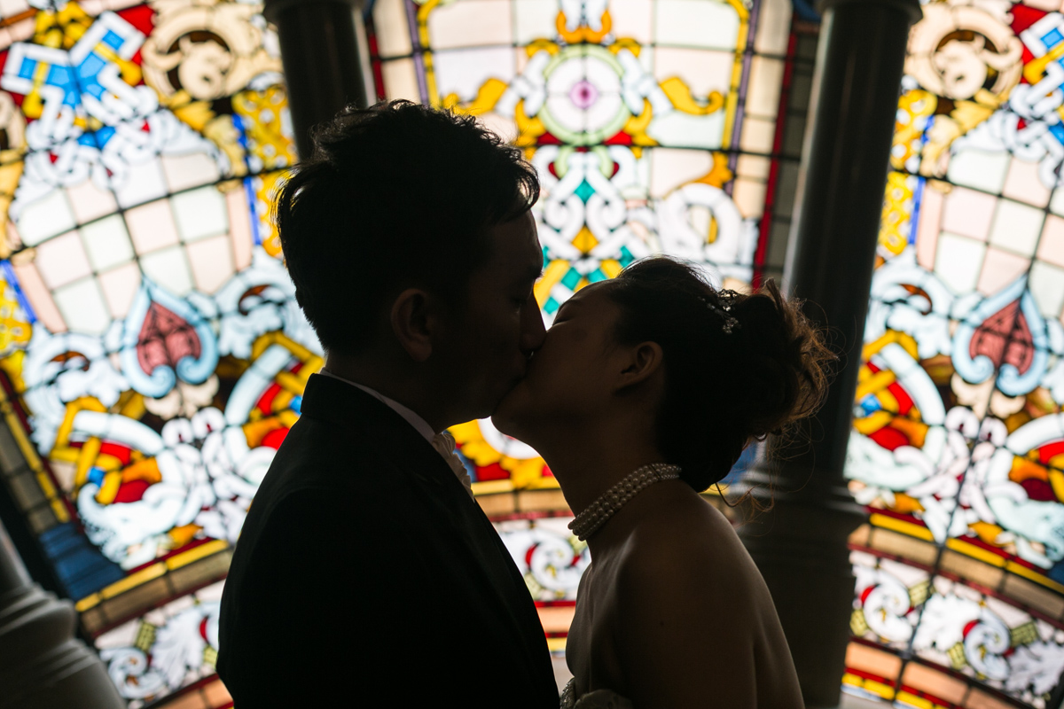 The bride and groom kiss silhouetted against the stained glass windows of the Queen Victoria Building Sydney wedding photographer