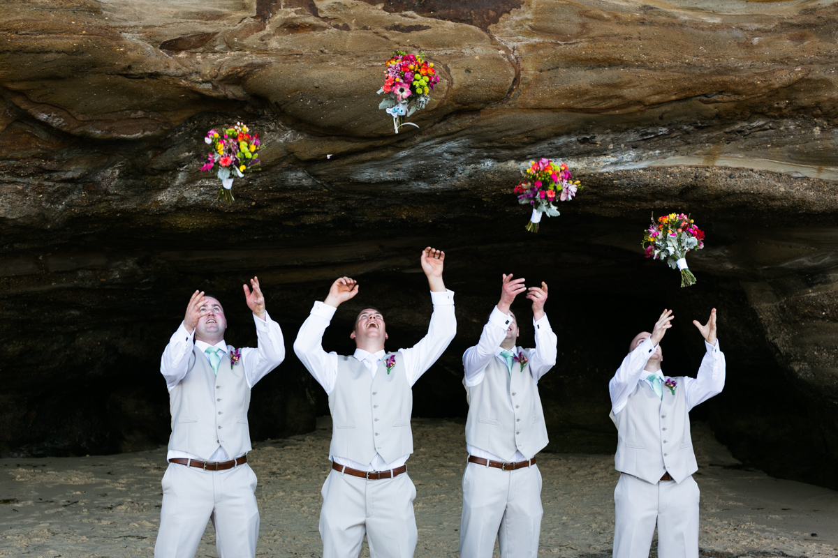 The groom and his groomsmen stand in a line in the mouth of a natural rock beach cave throwing the bridesmaid's multicoloured bouquets in the air Caves Beach wedding photography