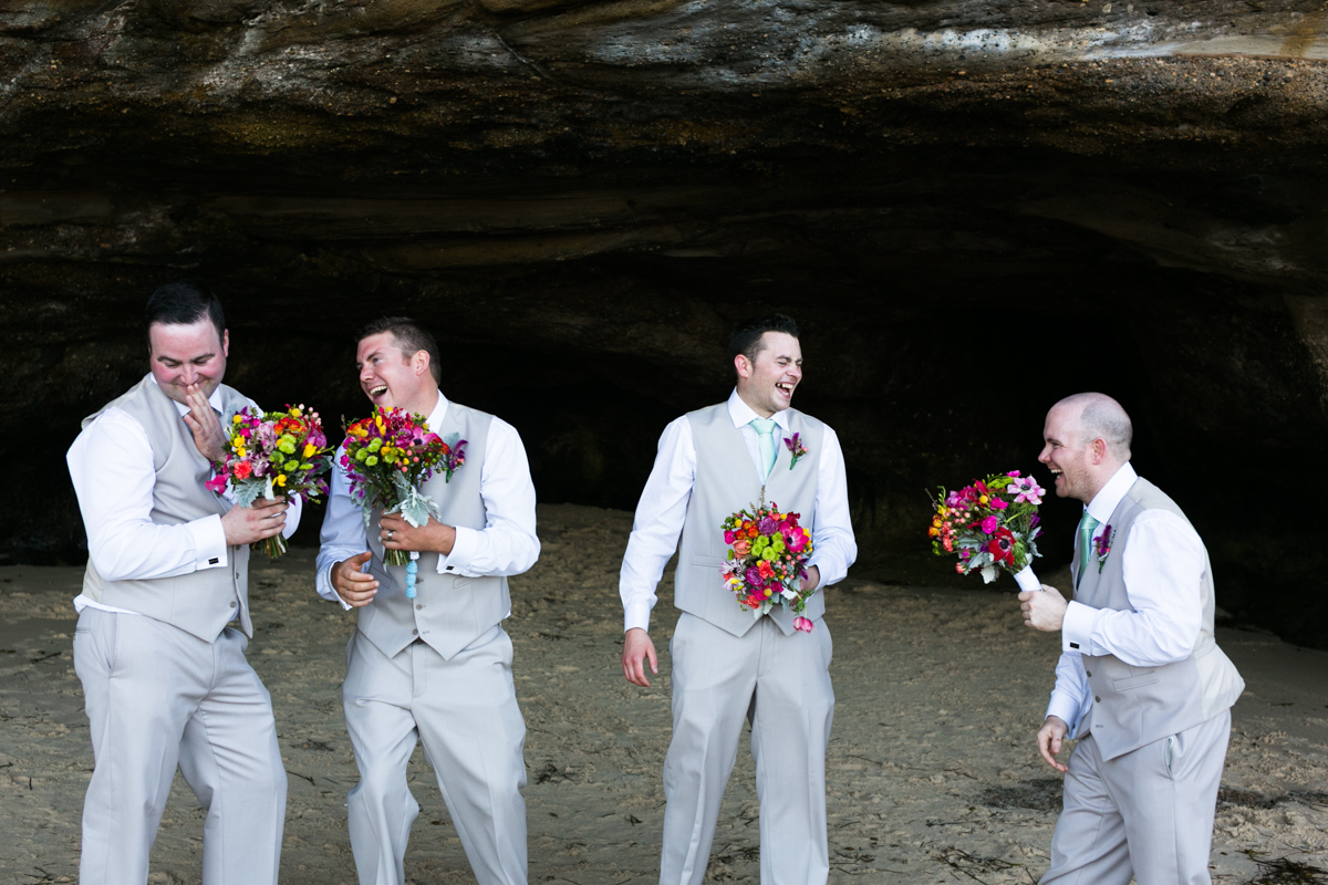 Candid shot of the groom and groomsmen being silly with the multicoloured bridal bouquets in the mouth of a beach cave Caves Beach wedding photography