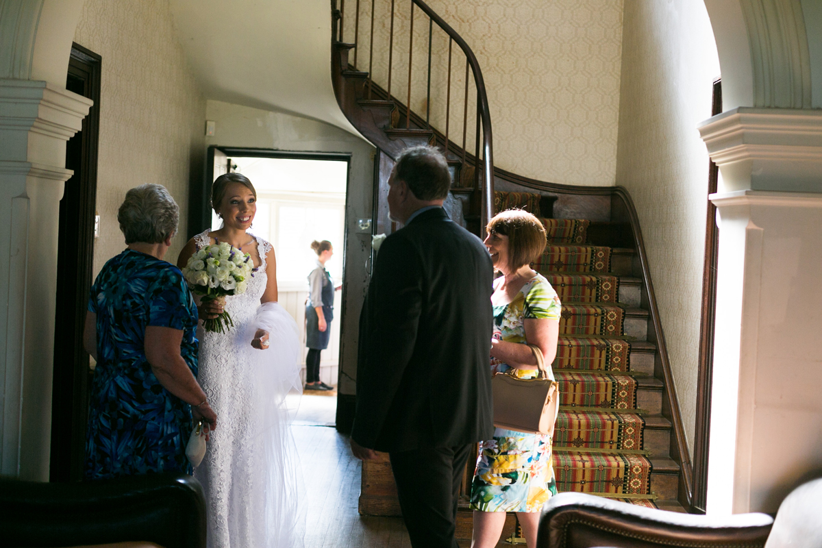Candid shot of the bride nervously talking to her family inside the Tocal Homestead at the bottom of the stairs before walking down the aisle at her Tocal Homestead wedding photographer