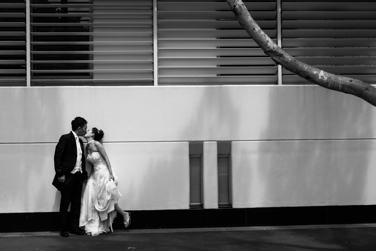 Black and white shot of the bride and groom kissing in front of an industrial commercial building wall Sydney wedding photographer