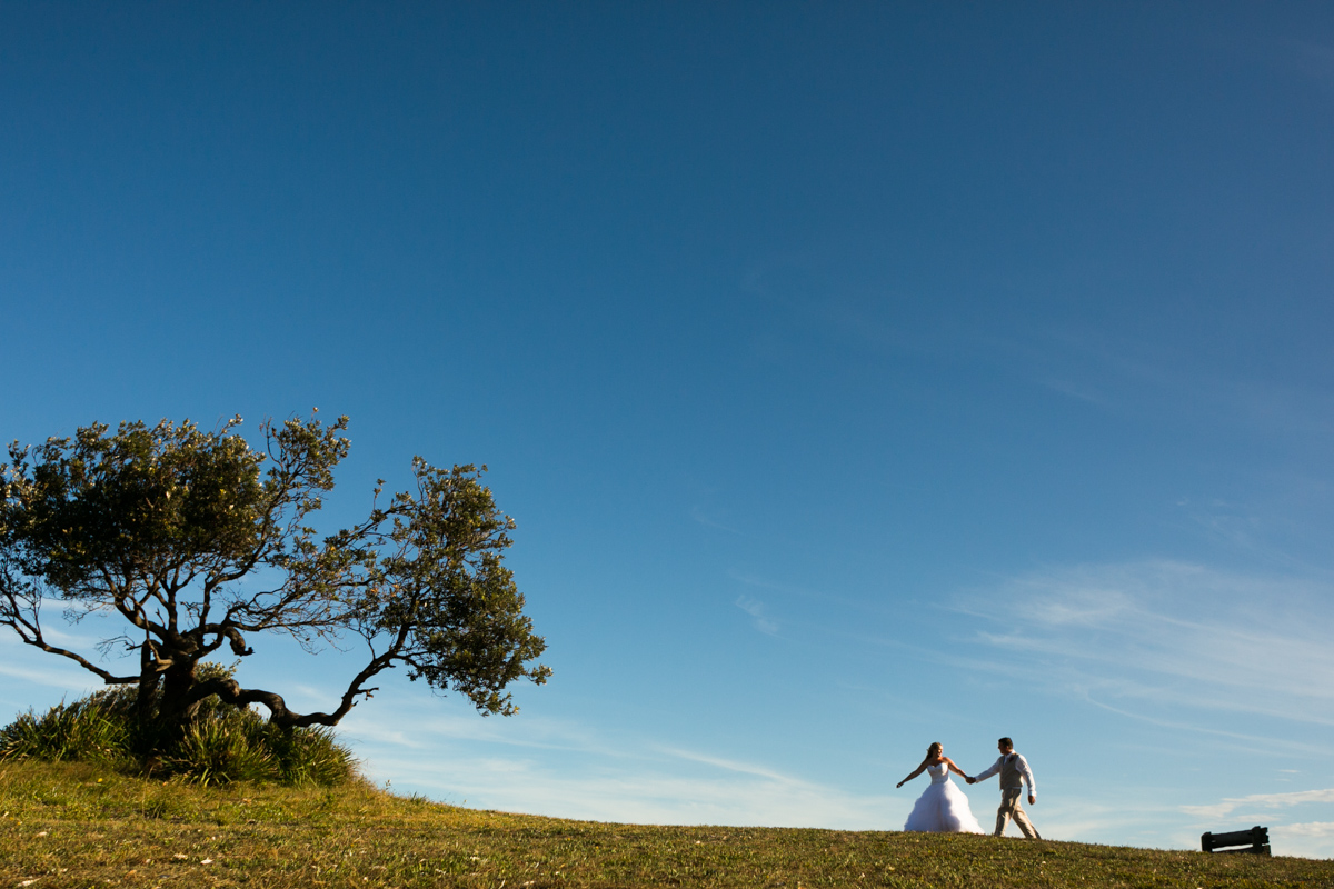 Landscape shot of the bride and groom holding hands walking up a green hill with clear blue skies behind Caves Beach wedding photography