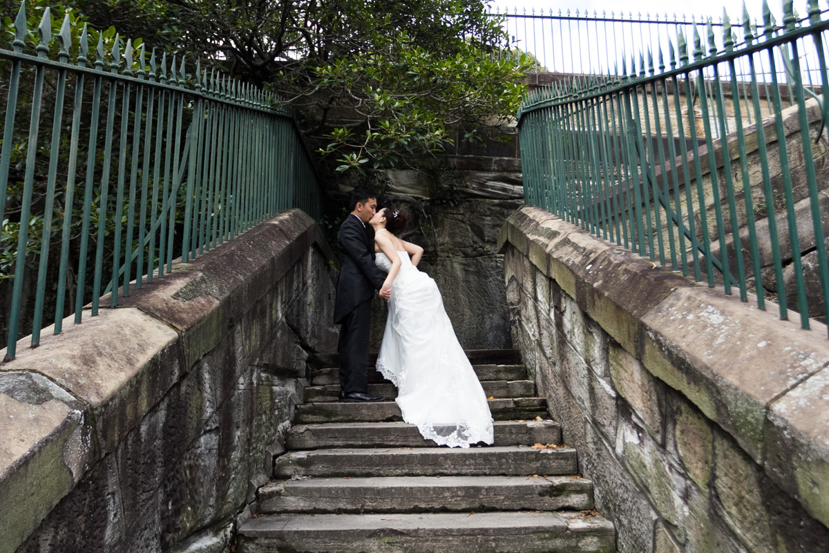 Shot of the bride and groom kissing looking up a set of old stone stairs surrounded by green iron fence Sydney wedding photographer