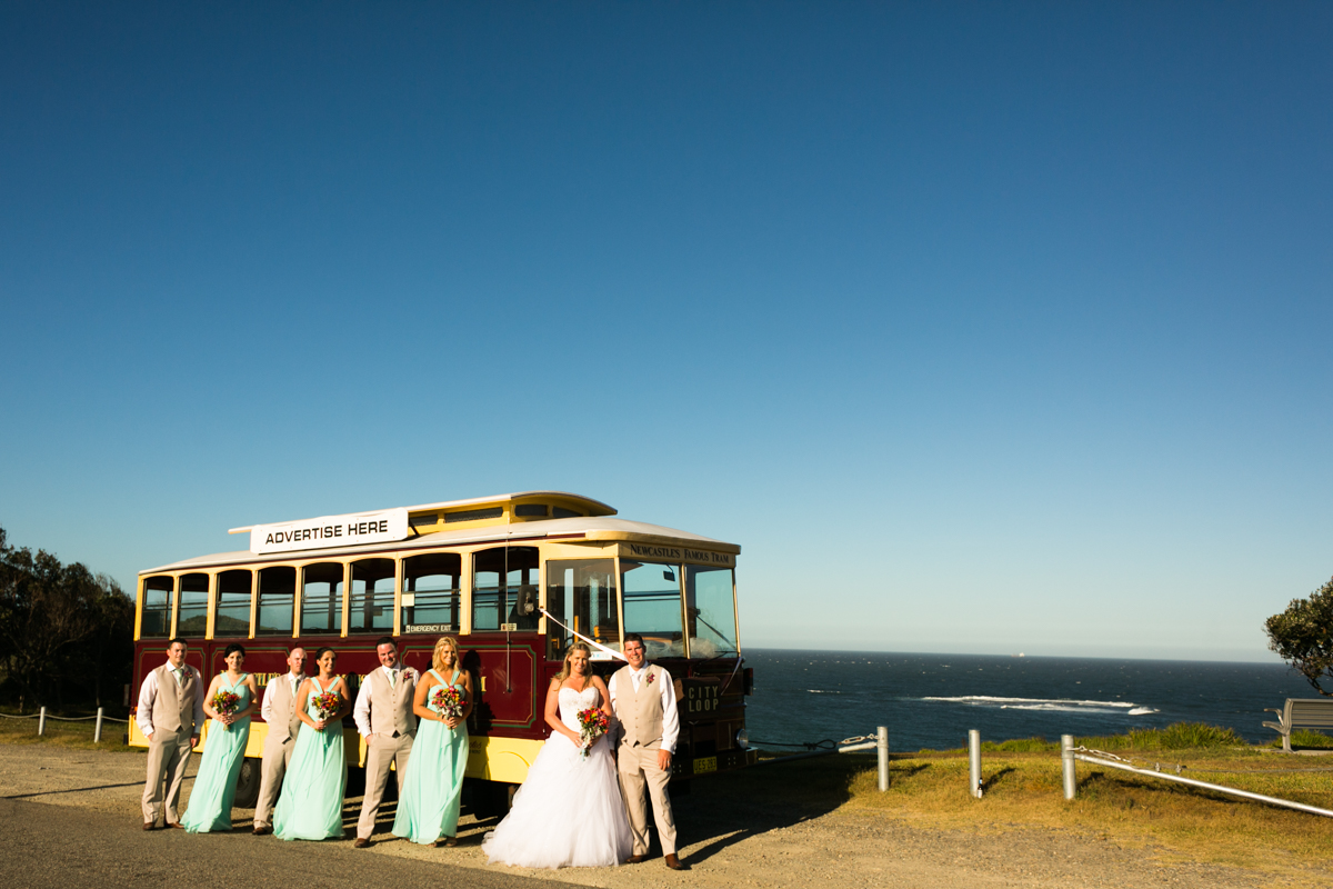 Landscape shot of the bride and groom standing with their bridal party in front of Newcastle's Famous Tram with the ocean and blue sky in the background Caves Beach wedding photography