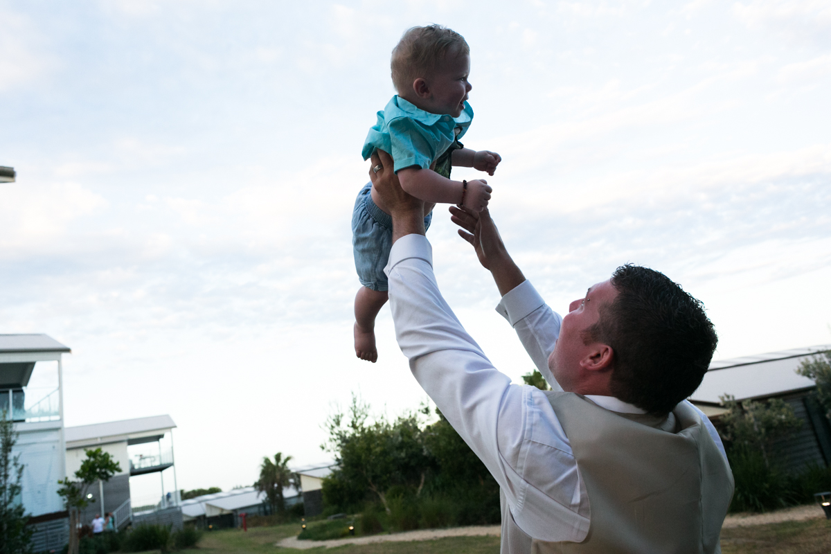 Candid shot of the groom tossing his young son into the air Caves Beach wedding photography