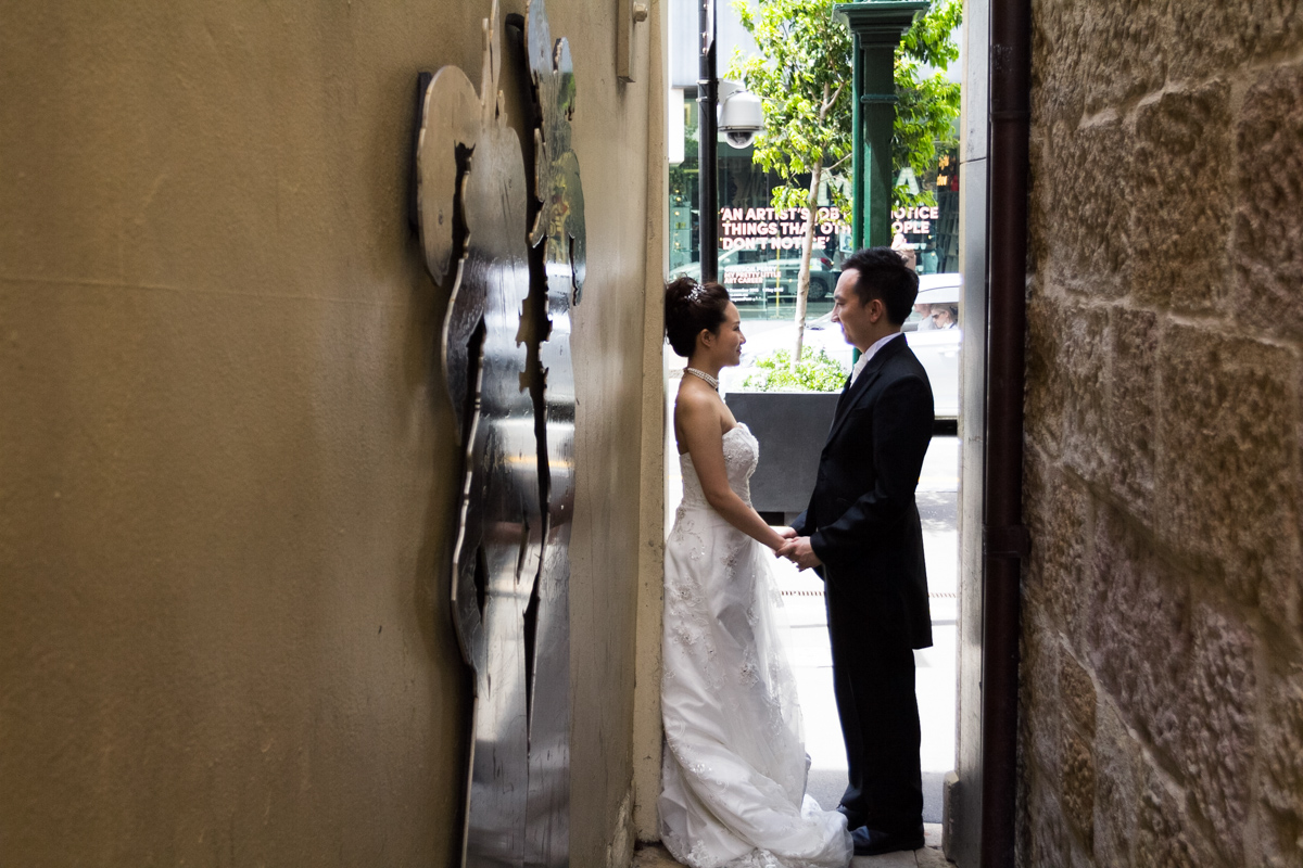 The bride and groom stand facing each other holding hands shot down the length of a brick and cement alleyway with a silver art installation on one wall Sydney wedding photographer