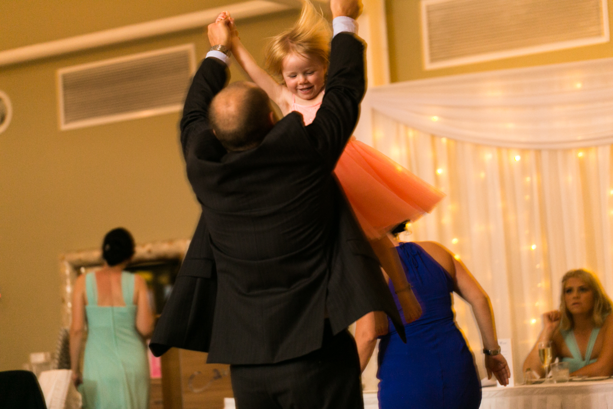 Candid action shot of a wedding guest lifting a small girl into the air and spinning her around on the dance floor Caves Beach wedding photography