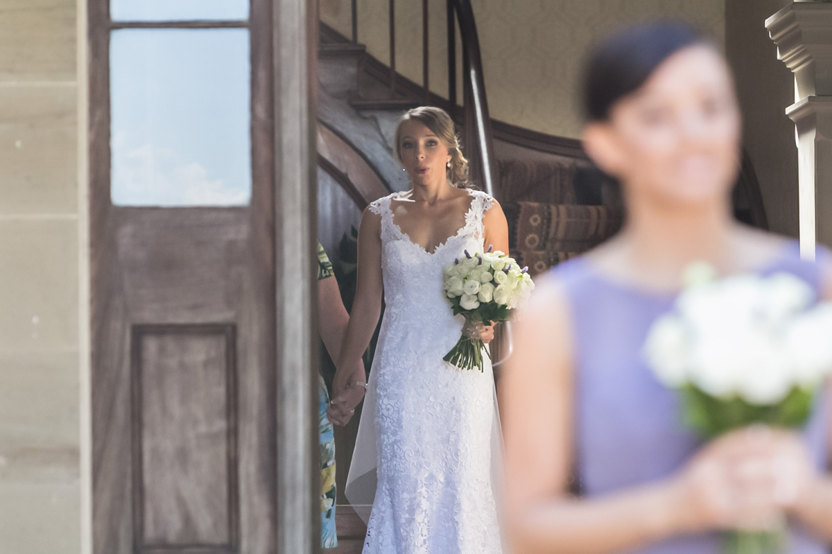 Candid shot over the bridesmaid's shoulder as the bride takes a deep breath before walking down the aisle at her Tocal Homestead wedding photographer