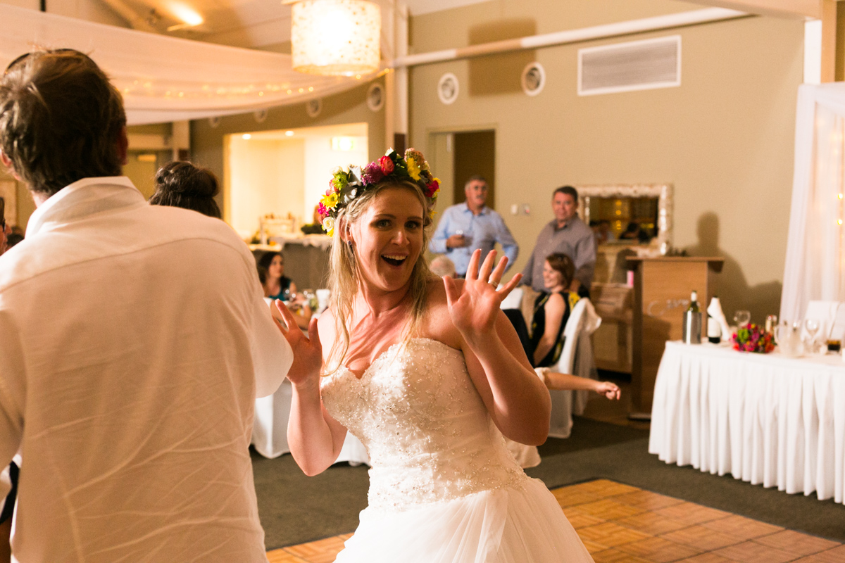 Candid shot of the bride on the dance floor pulling a face at the camera Caves Beach wedding photography