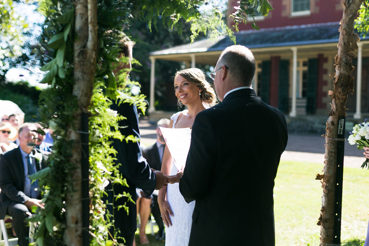 Candid shot of the bride and groom at the altar under the large green tree out the front of the Tocal Homestead shot through their floral and wooden bower Tocal Homestead wedding photographer