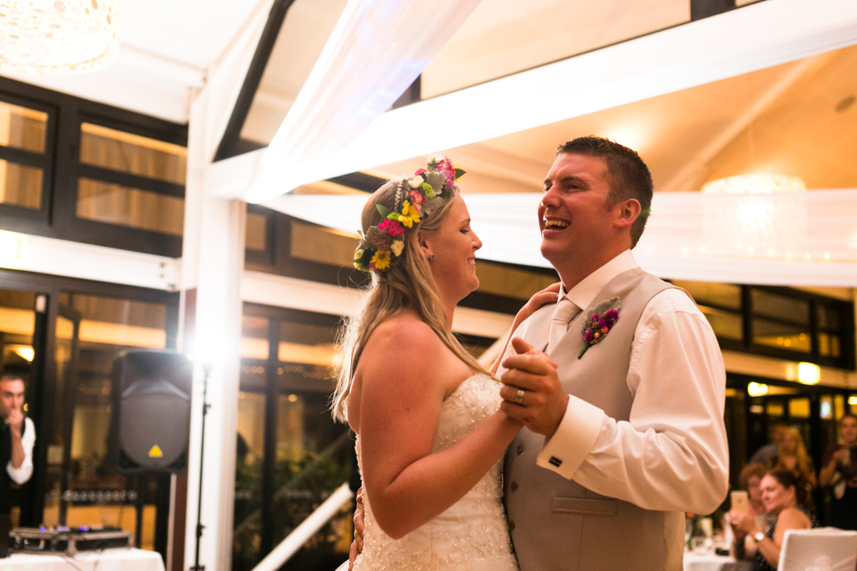 Action shot of the bride and groom on the dance floor during their first dance bride wearing a multicoloured flower crown Caves Beach wedding photography