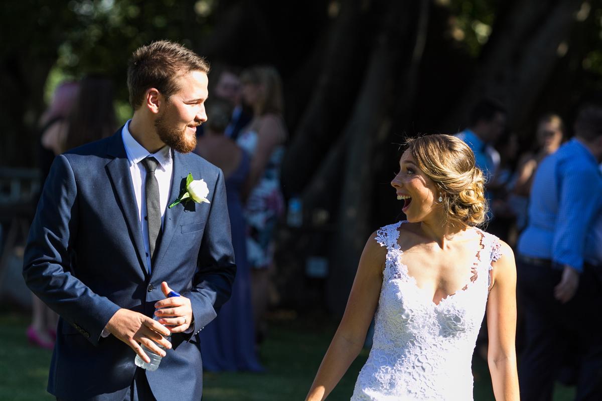 Candid shot of the bride and groom sharing excited looks as they walk back down the aisle at their Tocal Homestead wedding photographer