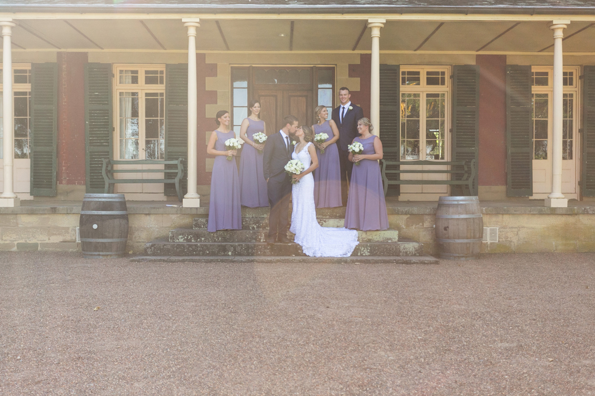 The bride and groom kiss on the steps of the Tocal Homestead verandah surrounded by their wedding party with sun streaming in from behind Tocal Homestead wedding photographer