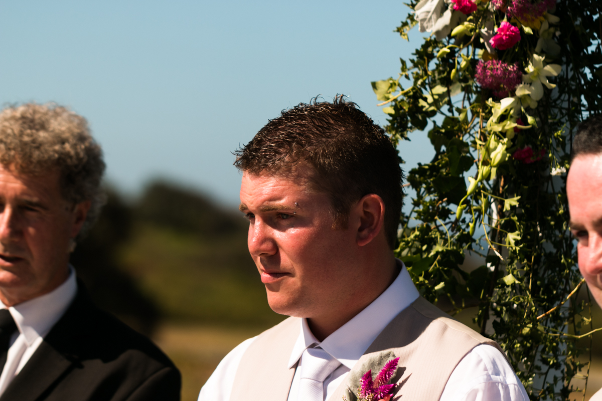 Close up of the groom's face as he sees his bride walk down the aisle for the first time Caves Beach wedding photography