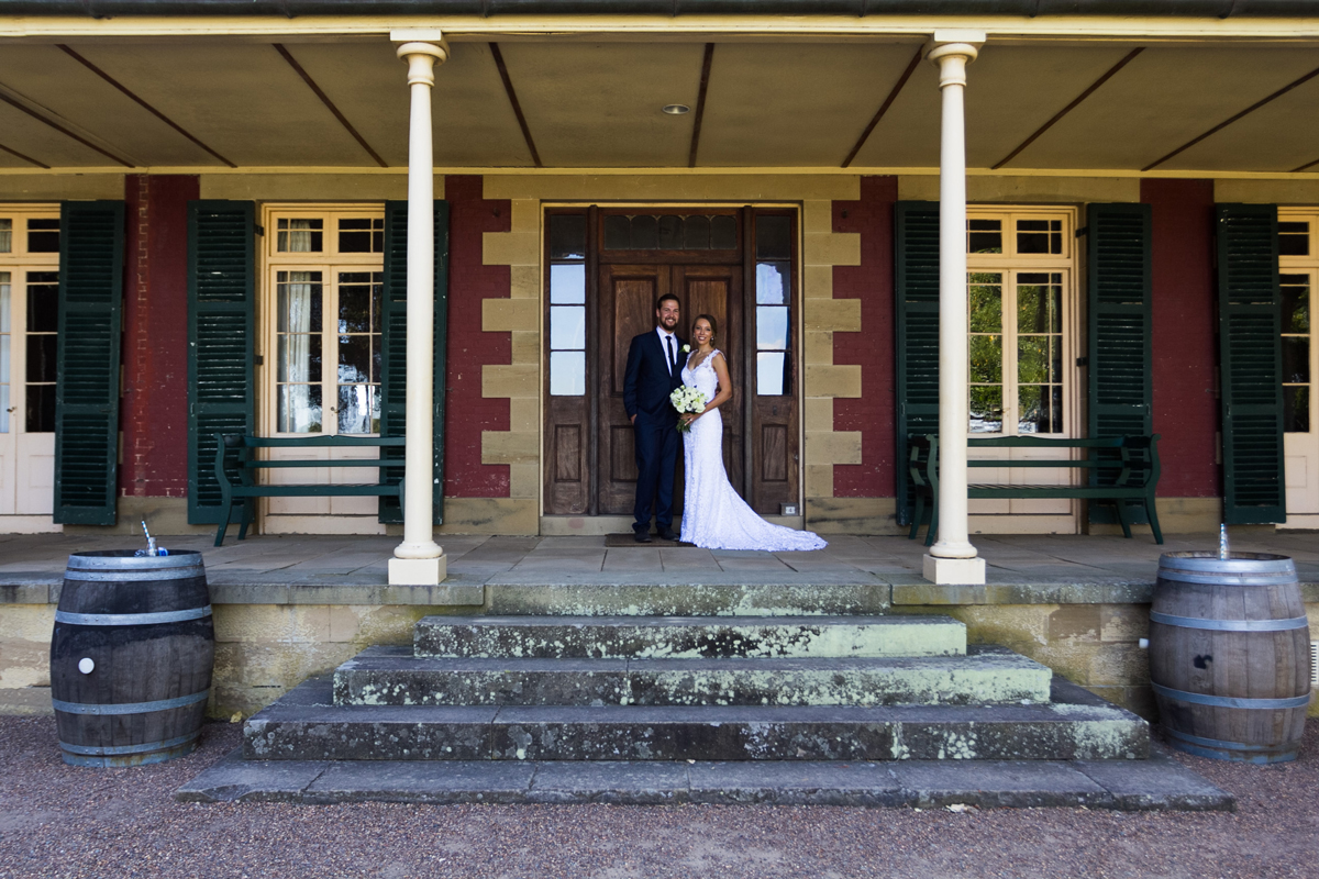 The bride and groom stand together on the verandah of the Tocal Homestead wedding photographer