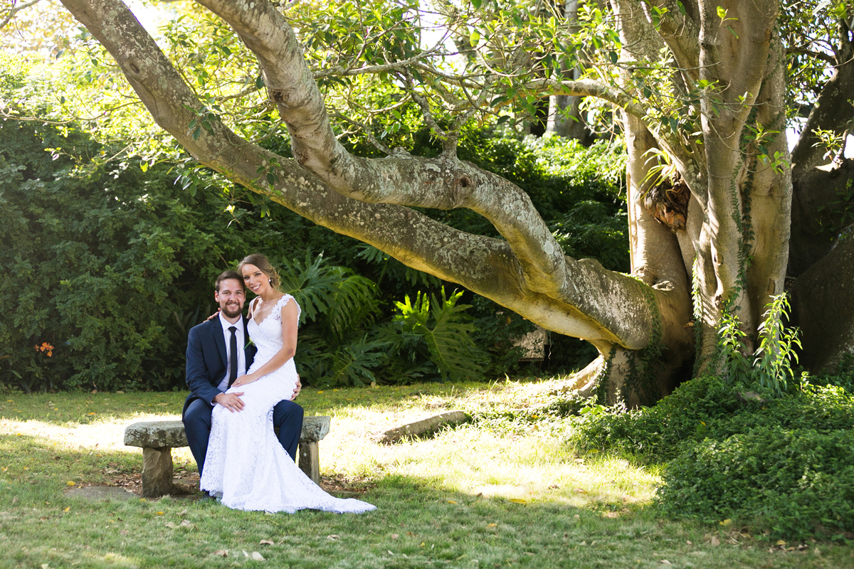 The bride sits on the groom's lap on a stone bench under the branches of a large tree in the grounds of Tocal Homestead wedding photographer